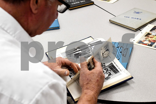Don Shubert flips through an old yearbook at a reunion during a high school football game at Hawkins High School in Hawkins, Texas, on Friday, Oct. 13, 2017. The 1967 regional championship football team reunited for Hawkins' homecoming game. (Chelsea Purgahn/Tyler Morning Telegraph)