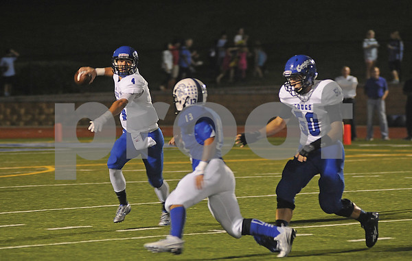 Cougars quarterback Chandler Nutt (4) evades the Trojans' defense as he attempts a pass on Friday, Oct. 17, 2014, during Grace Community's game against cross-town rival All Saints Episcopal at Mewbourne Field in Tyler. (Derek Kuhn/Staff)