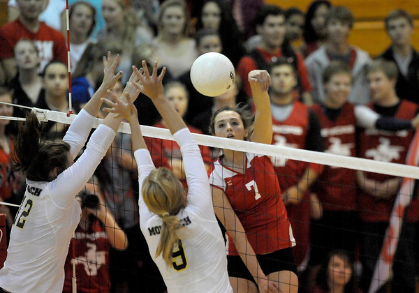 Fairview's Nicole Edelman (right) spikes the ball past Monarch's Hannah Safari (left) and Kendall Peterson during their volleyball game at Fairview High School in Boulder, Colorado October 18, 2011.  CAMERA/Mark Leffingwell