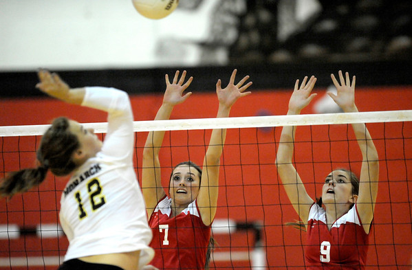 Fairview's Nicole Edelman (middle) and Alison Yardley (right) try to block Monarch's Hannah Safari (left) during their volleyball game at Fairview High School in Boulder, Colorado October 18, 2011.  CAMERA/Mark Leffingwell