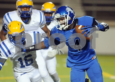 photo by Sarah A. Miller/Tyler Morning Telegraph  John Tyler High School senior DeQuante Woods carries the ball with Jacksonville's (16) close behind Friday night at Trinity Mother Frances Rose Stadium.