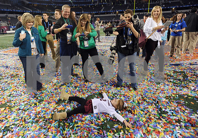 photo by Sarah A. Miller/Tyler Morning Telegraph  Kate Moore, 3, of College Station makes snow angels in the confetti on the field after Texas A&M won the AT&T Cotton Bowl Classic in Arlington Friday.