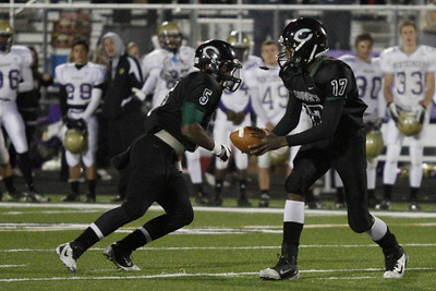 Connally's Landon Nobles passes the ball off to Shaun Williams against Montgomery in the first round of the Division 1 playoffs Friday at Cougar Stadium.