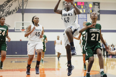 Hendrickson's Jakira Rogers, middle, drives to the hoop against Connally's Daijon Kirby at Hendrickson High School on Tuesday.