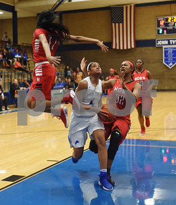 John Tyler's Alyssa Mayfield eyes the basket between Mesquite Horn's Nyah Boyd and (32) Umaja Collins as the Lady Lions play Mesquite Horn at home Tuesday Jan. 10, 2017.  (Sarah A. Miller/Tyler Morning Telegraph)