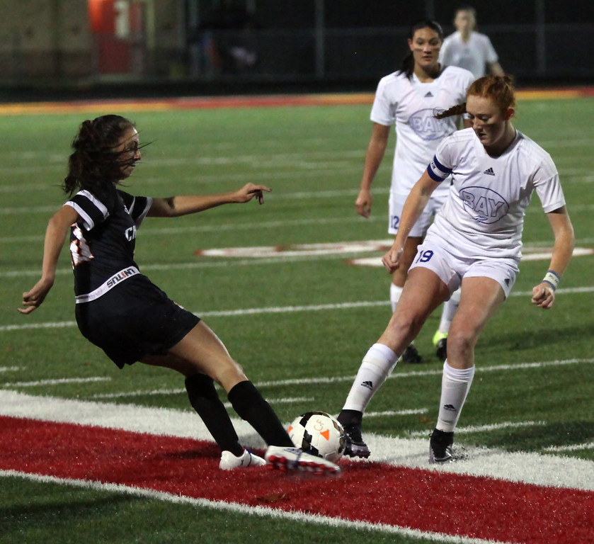 . Bay Maddie Holmes and Chagrin Falls\' Kelsey Taussig battle for possession of the ball. Randy Meyers -- The Morning Journal