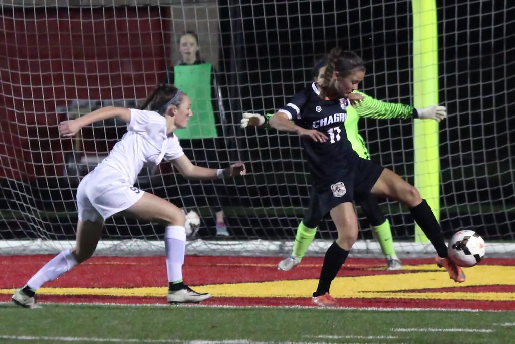 . Chagrin Falls\' Katie Schumacher kicks the ball away from her goal as Bay\'s Alex Hoffman closes in. Randy Meyers -- The Morning Journal