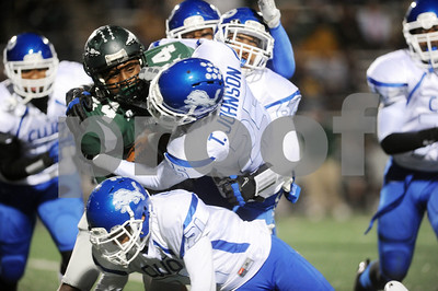 photo by Sarah A. Miller/Tyler Morning Telegraph  John Tyler's (25) senior Traven Johnson takes down Waxahachie's (24) junior Treyvon Hughes during the Class 4A Division I bi-district playoff game at Homer B. Johnson Stadium in Garland Friday night.