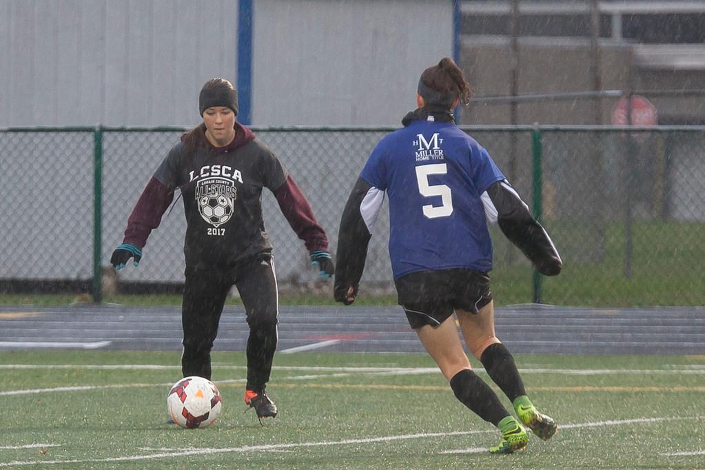 . Wellington\'s Emma Horoschak (Grey) has to pass Avon\'s Megan Sikora to move the ball down the field. Jen Forbus -- The Morning Journal