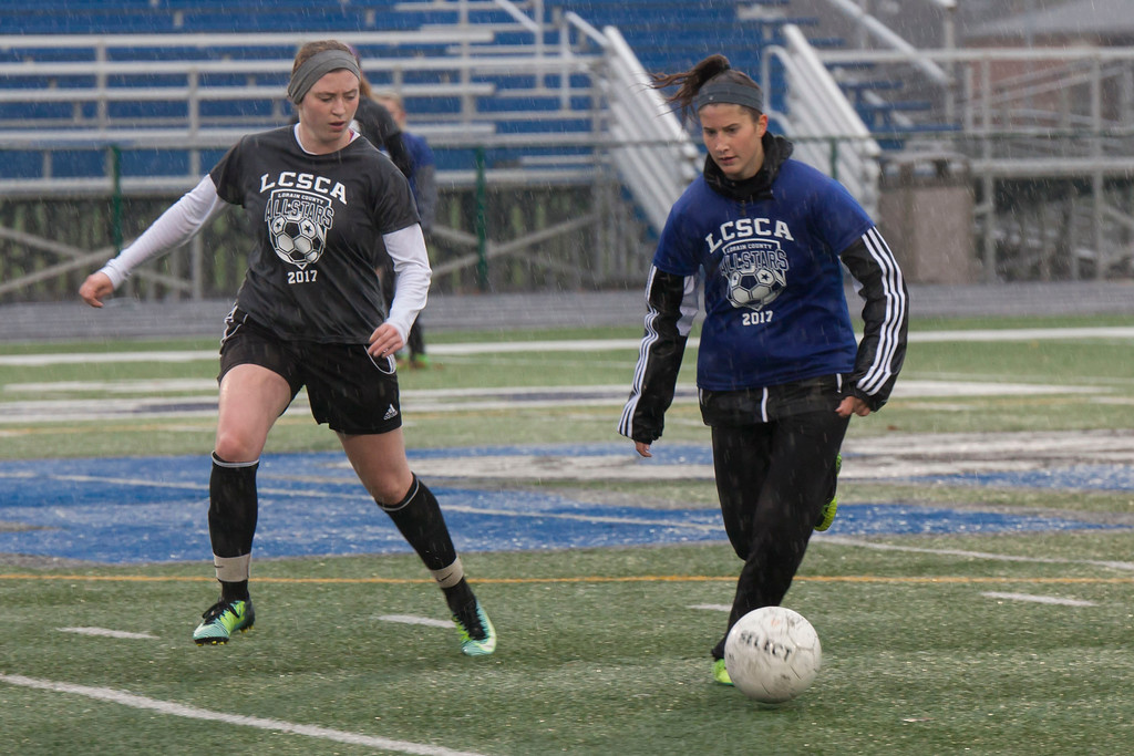 . Jen Forbus -- The Morning Journal Avon\'s Megan Sikora (Blue) controls the ball as Lake Ridge\'s Sydney Mayberry closes in.