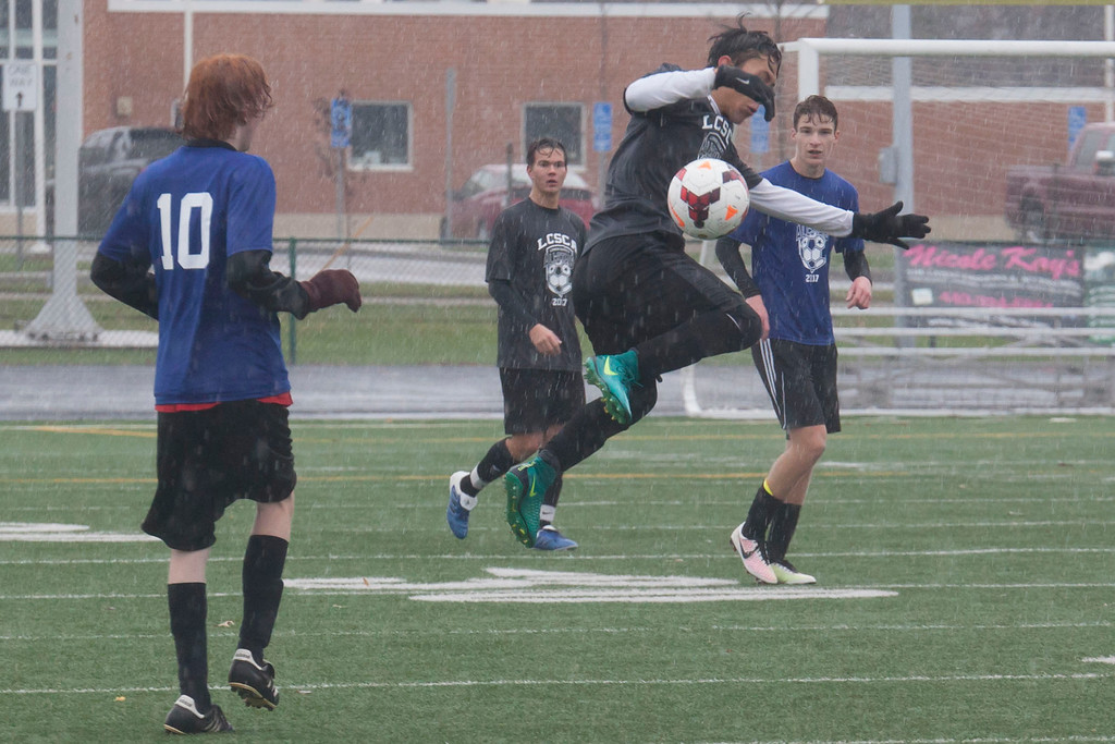 . Elyria Catholic\'s Matt Mickelson (Grey) gets vertical on the pitch. Jen Forbus -- The Morning Journal
