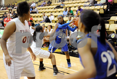 photo by Sarah A. Miller/Tyler Morning Telegraph  John Tyler's Tootie Johnson keeps the ball from Robert E. Lee's Tree Brooks during their game at Tyler Junior College's Wagstaff Gymnasium Tuesday afternoon. The John Tyler Lions won, 80-39.
