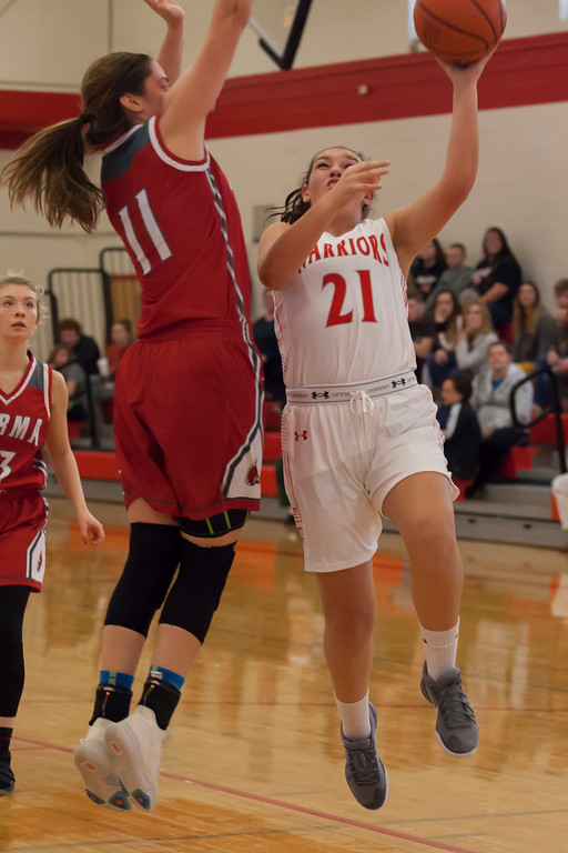 . The Warriors\' Gabby Biggs gets vertical for a layup as Parma\'s Lindsay Humbel tries to impede her shot. Jen Forbus -- The Morning Journal