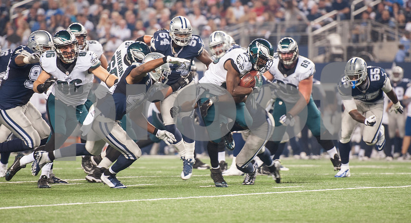 photo by Sarah A. Miller/ Tyler Morning Telegraph   Philadelphia Eagles running back LeSean McCoy (25) is brought down by Dallas' Barry Church (42) during their  Thursday Nov. 27, 2014 at AT&T Stadium in Arlington. The Eagles beat the Cowboys 33-10.