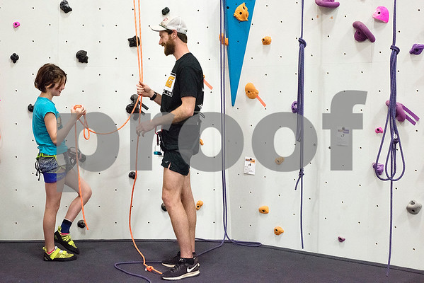 Navi Lee, 11, and Chris Thompson chat at the Tyler Rock Gym in Tyler, Texas, on Wednesday, Nov. 29, 2017. The new gym features up to 32-foot high walls, 12 auto belays, youth programs, bouldering and classes for beginners and seasoned climbers alike. (Chelsea Purgahn/Tyler Morning Telegraph)