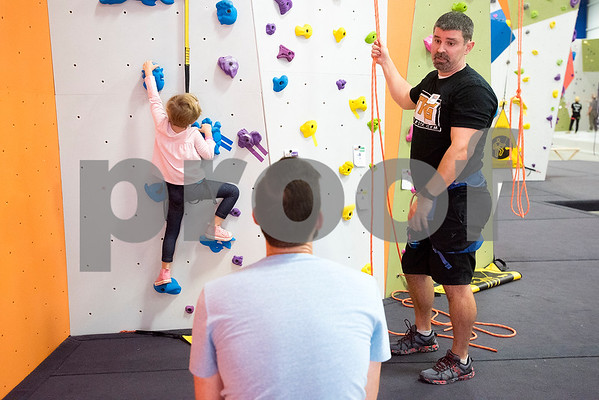 Shawn Wilson, right, talks to John Mather, center, as Mather's daughter London, 4, climbs at the Tyler Rock Gym in Tyler, Texas, on Wednesday, Nov. 29, 2017. The new gym features up to 32-foot high walls, 12 auto belays, youth programs, bouldering and classes for beginners and seasoned climbers alike. (Chelsea Purgahn/Tyler Morning Telegraph)