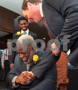 University of Houston quarterback Greg Ward, left, watches in the background current offensive coordinator and quarterbacks coach for Houston Major Applewhite, right, shakes hands with Earl Campbell during the Earl Campbell Tyler Rose Award banquet Wednesday Jan. 13, 2016 at Willow Brook Country Club in Tyler, Texas. The Earl Campbell Tyler Rose Award recognizes the top offensive player in Division I football who also exhibits the enduring characteristics that define 1977 Heisman Trophy winner Earl Campbell: integrity, performance, teamwork, sportsmanship, drive, tenacity and community. Ward won the award.  (Sarah A. Miller/Tyler Morning Telegraph)