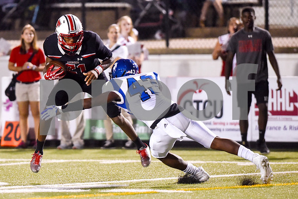 Robert E. Lee running back Ladarius Wickware (21) jumps to try and avoid a tackle from North Mesquite Kevion Curry (43) during a high school football game at Christus Trinity Mother Frances Rose Stadium in Tyler, Texas, on Friday, Nov. 3, 2017. (Chelsea Purgahn/Tyler Morning Telegraph)