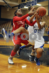 photo by Sarah A. Miller/Tyler Morning Telegraph  John Tyler's (22) Kay-Ana Tatum fights with Terrell's (4), Amber Brown, left, for control of the ball Monday night in Tyler. John Tyler won, 83-46.