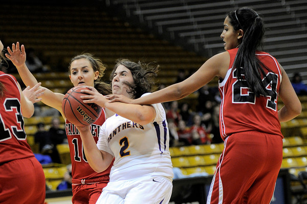 Sandwiched between Fairview's Meghan Higgins (left) and Sonia Ghosh (right) Boulder's Vivi Gregorich (middle) is fouled by Ghosh during their basketball game the University of Colorado in Boulder, Colorado January 17, 2011. CAMERA/MARK LEFFINGWELL