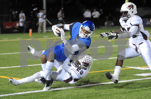 photo by Sarah A. Miller/Tyler Morning Telegraph  John Tyler's senior wide receiver Justice Liggins is taken down by Whitehouse's (28) Christopher Reese during their game at Trinity Mother Frances Rose Stadium Friday night in Tyler.