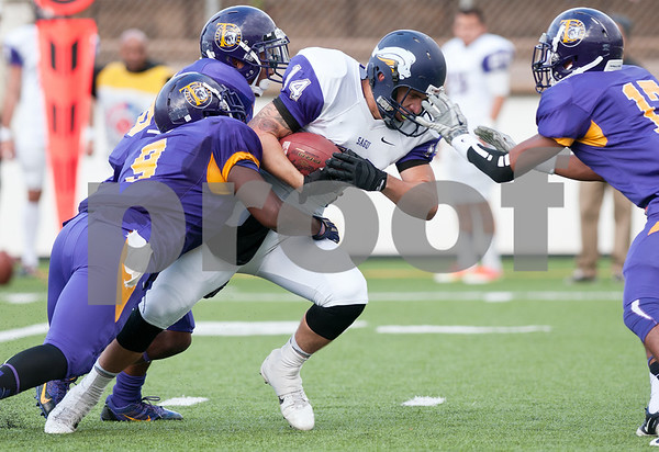 photo by Sarah A. Miller/Tyler Morning Telegraph  Texas College players (9), (28) and (17) at left, stop Southwestern Assemblies of God University's (14) tight end Dylan Moore Saturday afternoon at Trinity Mother Frances Rose Stadium in Tyler.