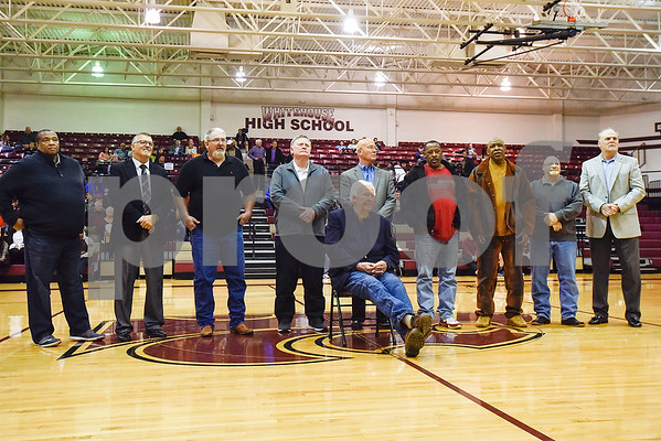 C.L. Nix sits as his 1978 championship team stands behind him during a ceremony recognizing the renaming of Whitehouse's arena to the C.L. Nix Wildcat Arena at Whitehouse High School in Whitehouse, Texas, on Friday, Jan. 19, 2018. The ceremony took place on the 40th anniversary of Coach Nix and the Wildcats winning a state championship in the 2A division in 1978. (Chelsea Purgahn/Tyler Morning Telegraph)