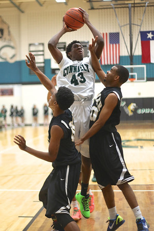 Connally's  Ishmael Donzo rises above a pair of Lanier defenders to take a shot at Connally High School on Monday.