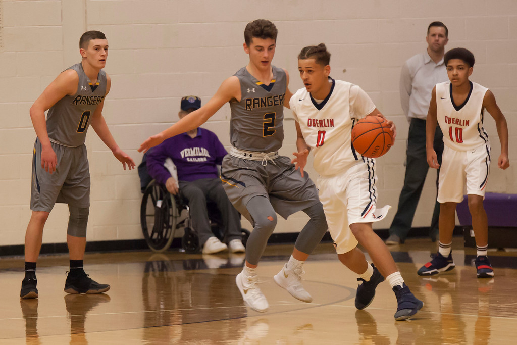 . Oberlin\'s Greg Richardson dribbles by North Ridgeville\'s Scoti Millgard toward the hoop.Jen Forbus -- The Morning Journal