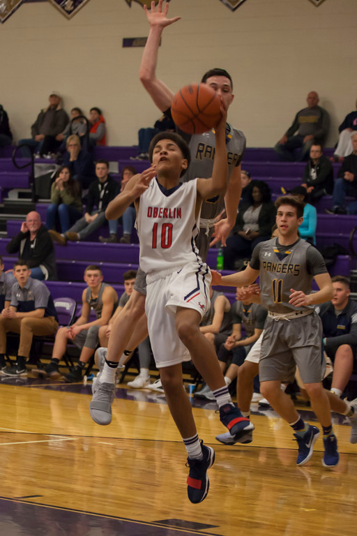 . Oberlin\'s Giles Harrell tries to take the ball to the hoop but North Ridgeville\'s Jeremy Sanchez has other plans. Jen Forbus -- The Morning Journal