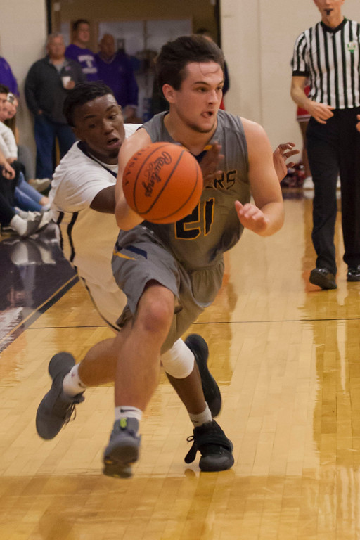 . North Ridgeville\'s Jason Vrba takes Oberlin\'s Justin Smith along for a ride to the basket.Jen Forbus -- The Morning Journal