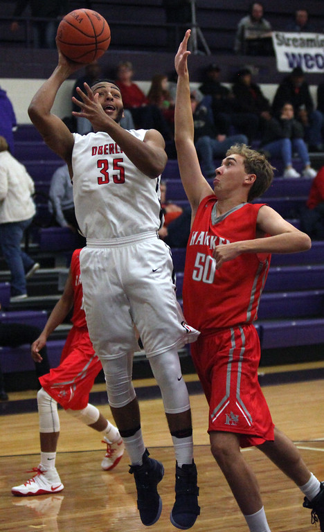 . Oberlin\'s Donald Johnson shoots over Anderson Clyde of Hawken during the first quarter of the Liberty Ford Tip-Off Classic. Randy Meyers -- The Morning Journal