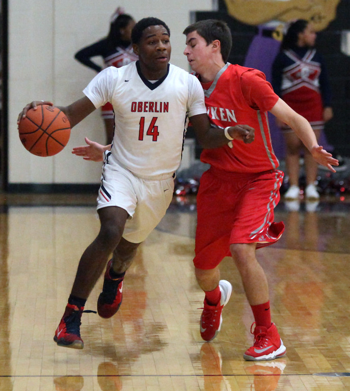 . Oberlin\'s Mark Robinson brings the ball up court against the pressure applied by Hawken\'s Jimmy Clark. Randy Meyers -- The Morning Journal