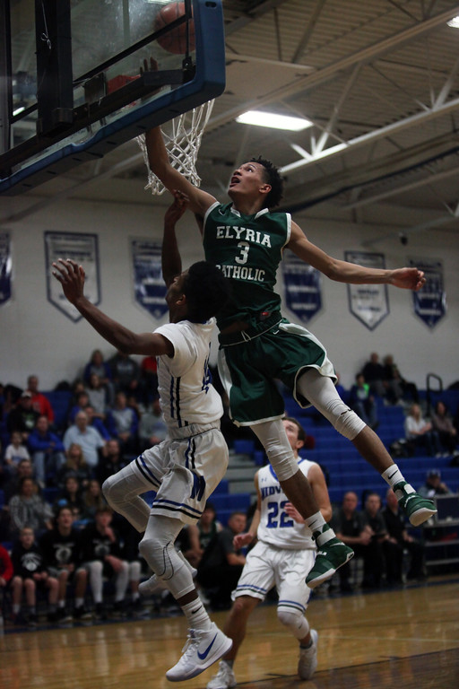 . Dorian Crutcher of Elyria Catholic goes up high to alter the shot by Midview\'s Isiah Johnson during the second quarter. Randy Meyers -- The Morning Journal