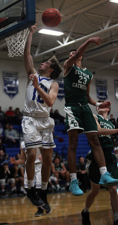 . Jarred Logan of Elyria Catholic blocks the shot by Seamus Higley of Midview. Randy Meyers -- The Morning Journal