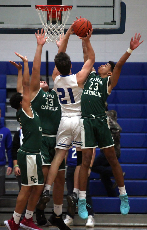. Midview\'s Gage Carnes shoots over Jarred Logan and Branson Taylor of Elyria Catholic during the first quarter. Randy Meyers -- The Morning Journal