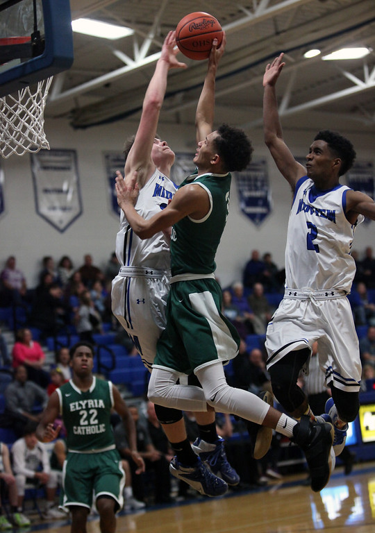 . Elyria Catholic\'s Dorian Crutcher is fouled on a drive to the basket by Gage Cames and Damian Malone of Midview during the Bob DiFranco Memorial Tournament. Randy Meyers -- The Morning Journal