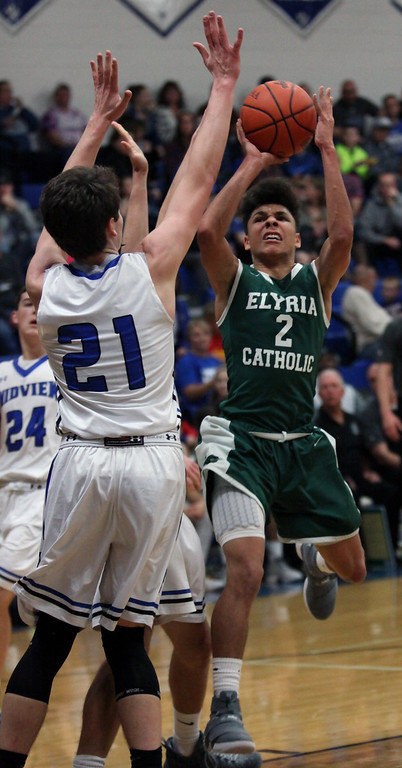 . Elyria Catholic\'s Donovan Warfield attempts a shot over Gage Cames of Midview at the Bob DiFranco Memorial Tournament. Randy Meyers -- The Morning Journal