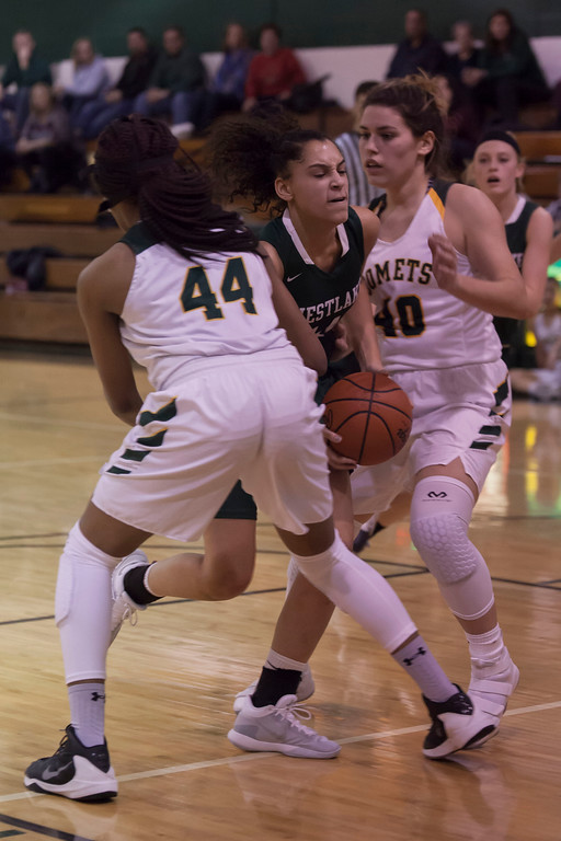 . Westlake\'s Abby Carrington tries to drive through a wall of Comets: Jill Wood (40) and Amaya Staton (44). Jen Forbus -- The Morning Journal