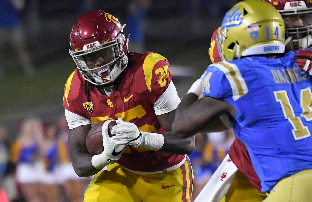 . Southern California running back Ronald Jones II, left, runs the ball as UCLA linebacker Krys Barnes defends during the second half of an NCAA college football game, Saturday, Nov. 18, 2017, in Los Angeles. USC won 28-23. (AP Photo/Mark J. Terrill)
