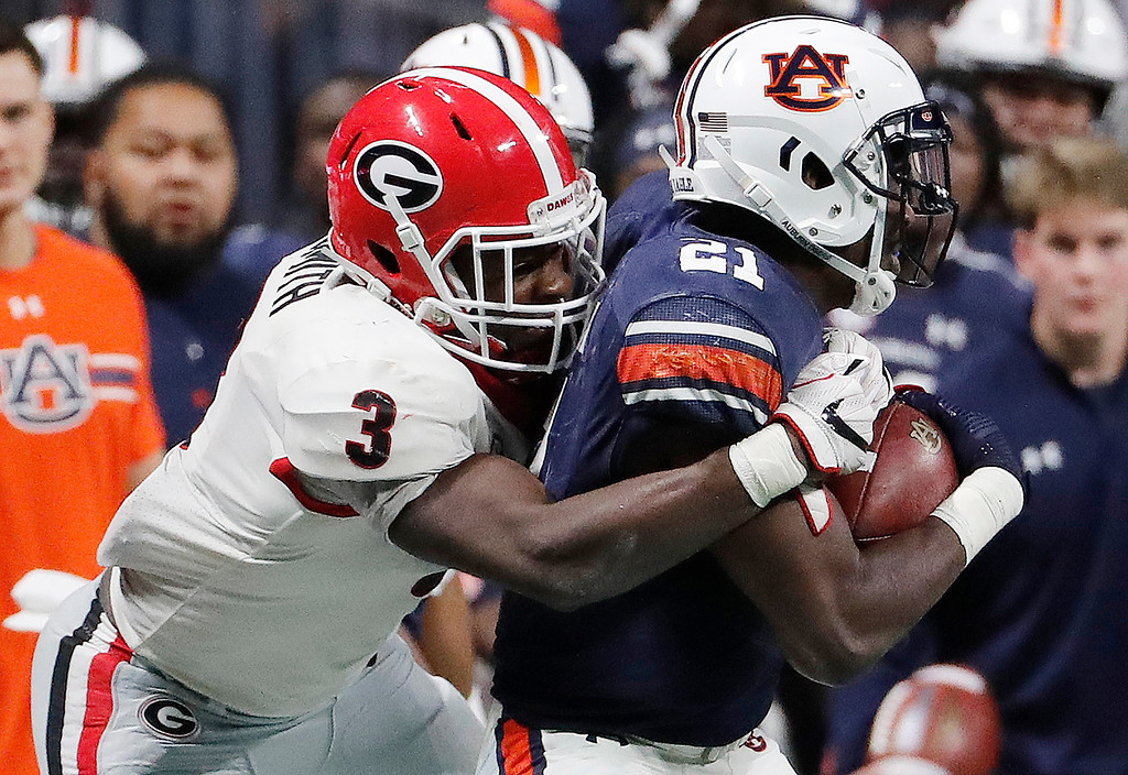 . Georgia linebacker Roquan Smith (3) tackles Auburn running back Kerryon Johnson (21) during the second half of the Southeastern Conference championship NCAA college football game, Saturday, Dec. 2, 2017, in Atlanta. (AP Photo/David Goldman)