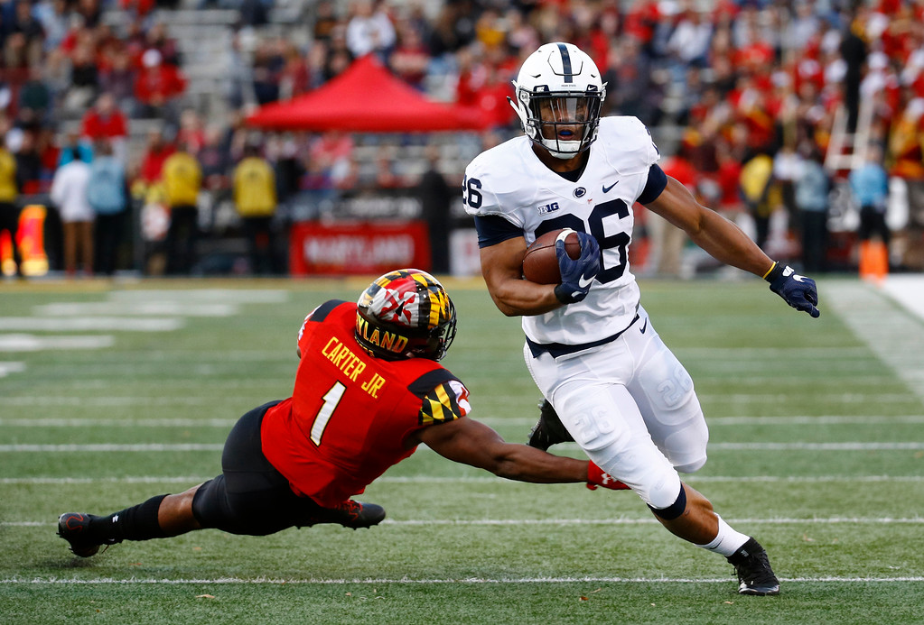 . Penn State running back Saquon Barkley, right, rushes past Maryland linebacker Jermaine Carter Jr. in the first half of an NCAA college football game in College Park, Md., Saturday, Nov. 25, 2017. (AP Photo/Patrick Semansky)