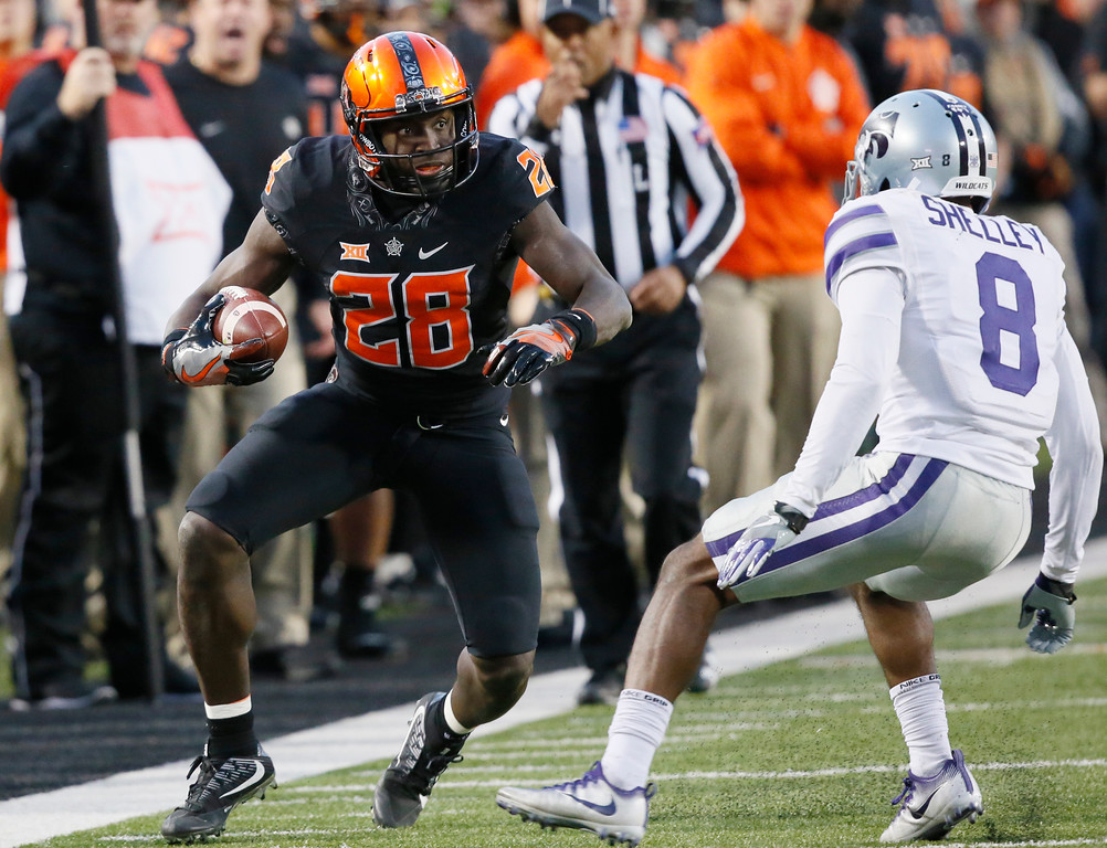 . Oklahoma State wide receiver James Washington (28) attempts to avoid a tackle by Kansas State defensive back Duke Shelley (8) in the second half of an NCAA college football game in Stillwater, Okla., Saturday, Nov. 18, 2017. Kansas State won 45-40.(AP Photo/Sue Ogrocki)