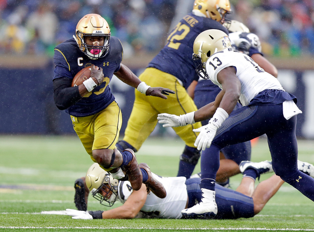 . Notre Dame running back Josh Adams (33) goes around Navy safety Juan Hailey (13) during the first half of an NCAA college football game in South Bend, Ind., Saturday, Nov. 18, 2017. (AP Photo/Michael Conroy)