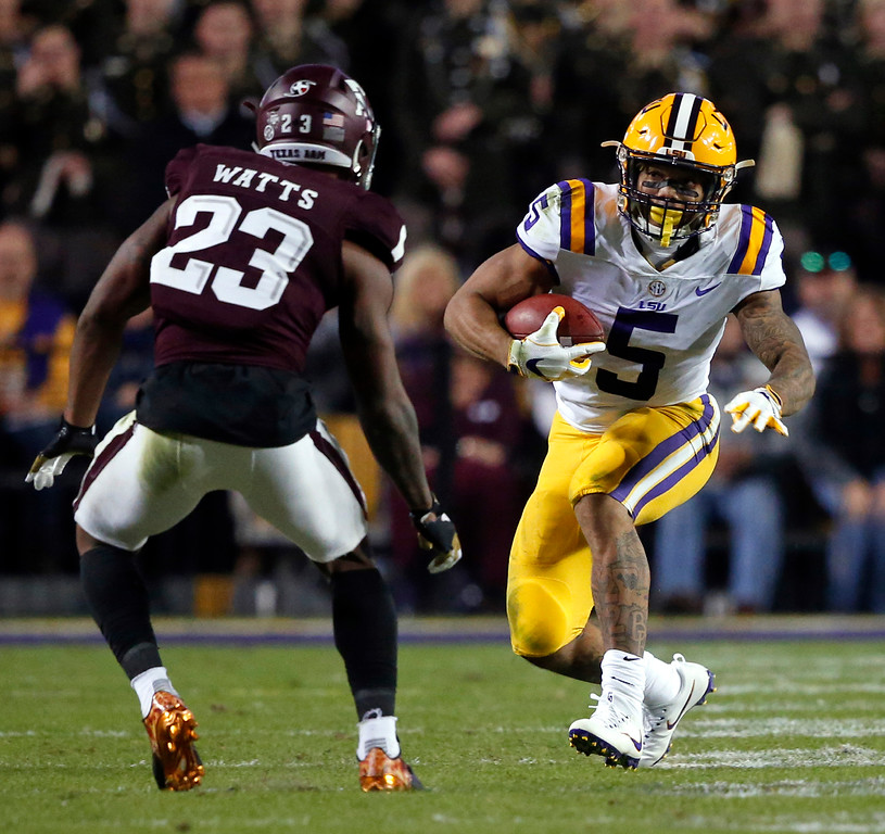 . LSU running back Derrius Guice (5) carries as Texas A&M defensive back Armani Watts (23) looks to make a tackle during the first half of an NCAA college football game in Baton Rouge, La., Saturday, Nov. 25, 2017. (AP Photo/Gerald Herbert)