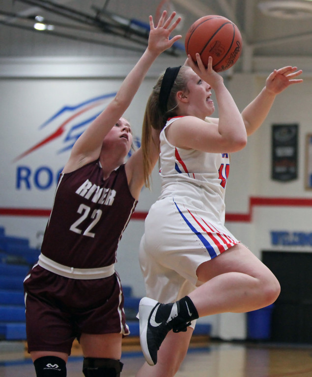 . Halle Orr of Bay takes a running one handed shot past Bridget McCue of Rocky River during the second quarter. Randy Meyers -- The Morning Journal