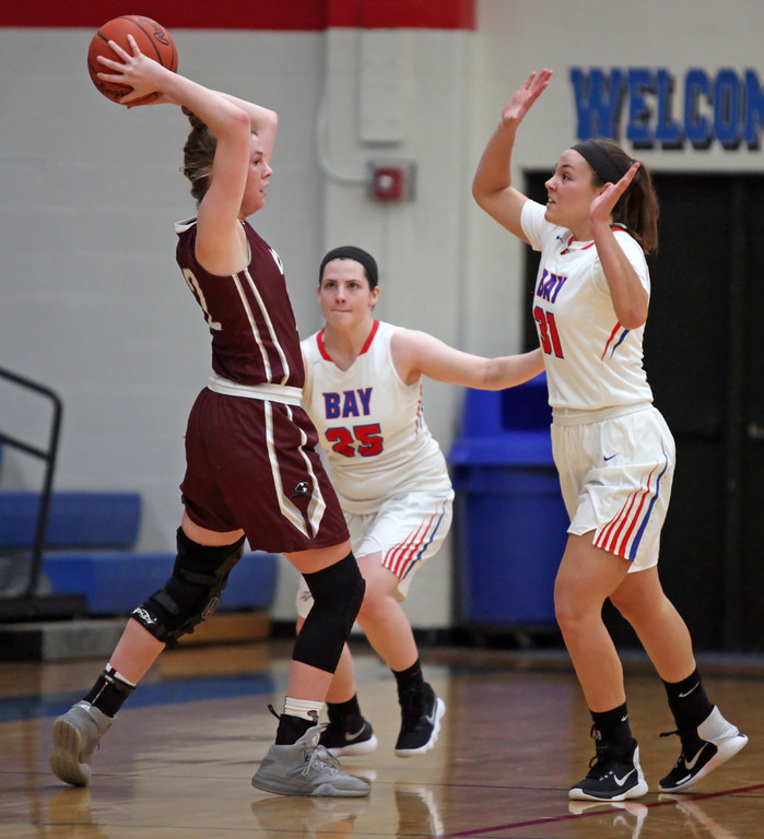 . Bridget McCue of Rocky River looks to pass away from a double team applied by Maddie Andrews, left,  and Maeve Johnston of Bay. Randy Meyers -- The Morning Journal