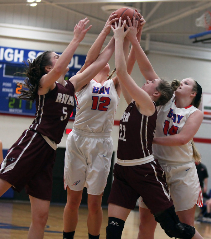 . Anne Beirne and Bridget McCue of Rocky River battle Maddie Edgerly and Halle Orr of Bay for a rebound during the second quarter. Randy Meyers -- The Morning Journal