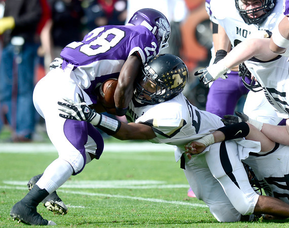 Monarch's Peter Mitchell (right) stops Denver South's Pete Williams (left) for a loss during their 4A State Football Championship football game in Denver, Colorado December 1, 2012. BOULDER DAILY CAMERA/ Mark Leffingwell