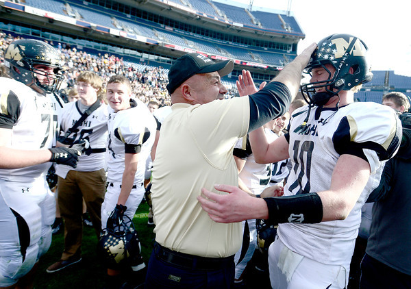 Coach Gary Creek (left) slaps Monarch's Cole Watson (right) on the helmut in celebration after winning the 4A State Football Championship football game against Denver South in Denver, Colorado December 1, 2012. BOULDER DAILY CAMERA/ Mark Leffingwell